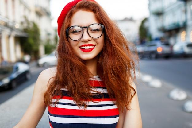Heureuse fabuleuse femme au gingembre en élégant béret rouge dans la rue