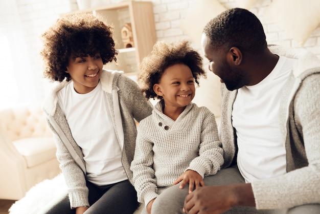 Heureuse famille africaine souriante assise sur un lit à la maison.