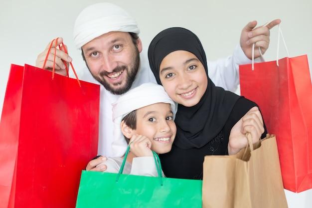 Heureuse famille arabe s'amuser avec des sacs à provisions