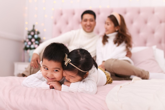 Heureuse famille asiatique avec deux enfants dans des chandails confortables et confortables s'amusant et se relaxant sur le lit