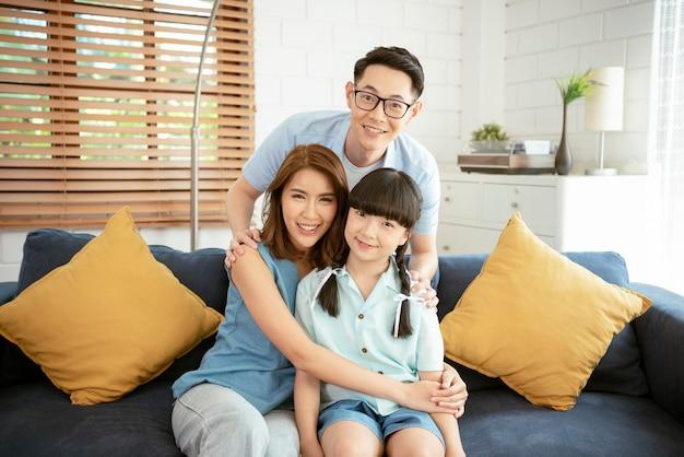 Heureuse famille asiatique étreignant ensemble sur le canapé au salon à la maison.