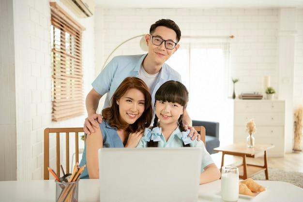 Heureuse famille asiatique étreignant ensemble dans le salon de la maison.