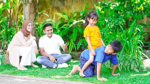 Heureuse famille asiatique jouant ensemble dans le parc