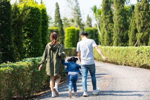 Heureuse famille asiatique marchant et tenant la main avec des enfants dans le parc. heureux père de famille mère et fille enfant