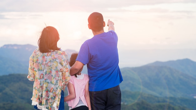 Heureuse famille asiatique père mère et fille debout au sommet de la belle montagne tenant mains levées