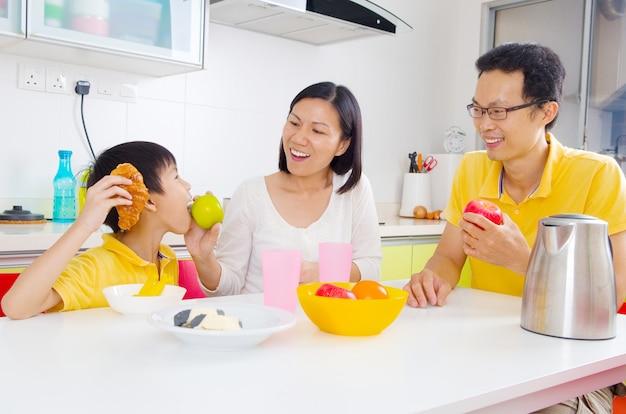 Heureuse famille asiatique prenant son petit déjeuner dans la cuisine