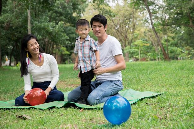 Heureuse famille asiatique profiter du temps en famille ensemble dans le parc. concept de famille