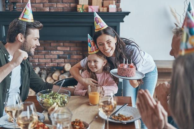 Heureuse famille célébrant l'anniversaire de la petite fille assise à la table à manger à la maison