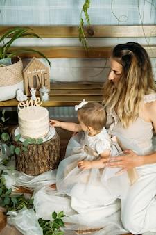 Heureuse famille célébrant le premier anniversaire de sa petite fille avec des idées de fête à la maison avec un gâteau pour le st anniversaire avec