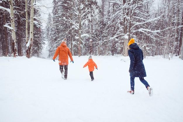 Heureuse famille courir dans la forêt de neige d'hiver