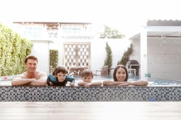Heureuse famille dans la piscine au parc aquatique en vacances s'amuser au bord de la piscine