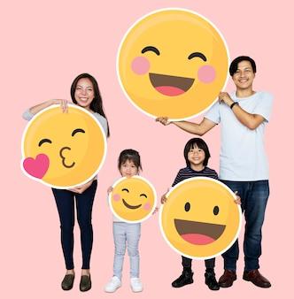 Heureuse famille détenant des icônes emoji