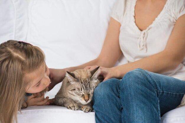 Heureuse famille de deux avec un chat assis sur le canapé et s'amuser