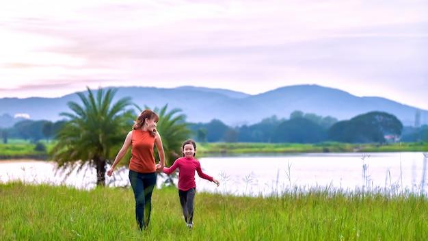 Heureuse famille de deux personnes, mère et enfant devant un ciel coucher de soleil.