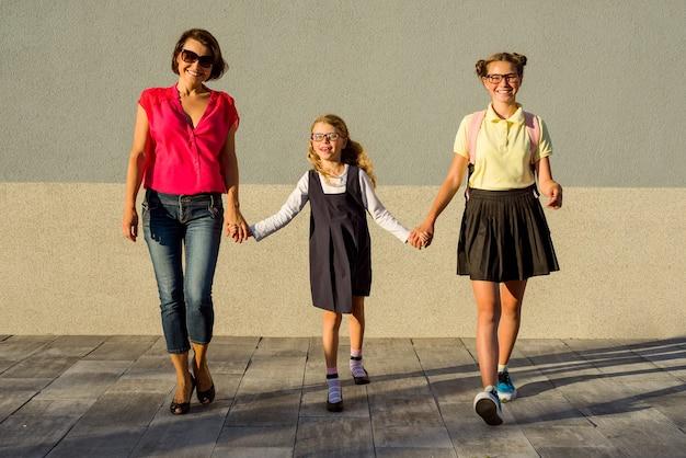 Heureuse famille écolière maman et sœurs tenant par la main
