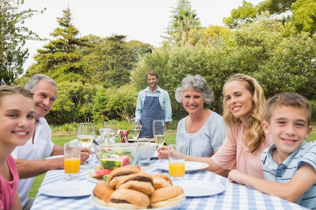 Heureuse famille élargie en attente de barbecue cuit par le père