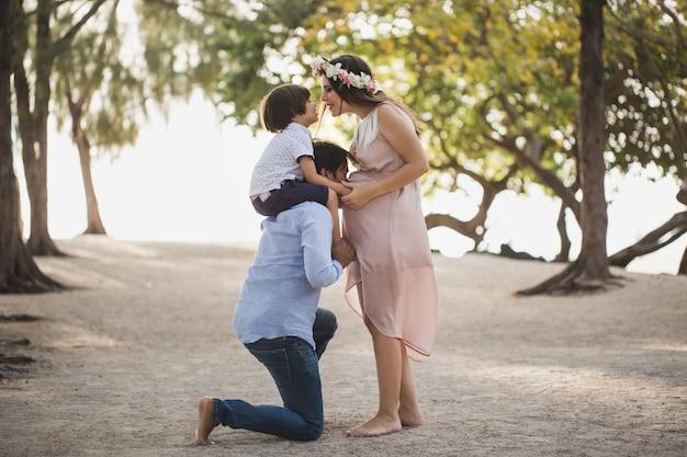 Heureuse famille enceinte s'amusant dans la nature. fils sur les épaules de ton père. papa embrasse sa femme enceinte dans le ventre.