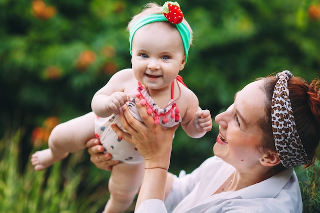 Heureuse famille harmonieuse à l'extérieur. mère jette bébé, rire et jouer en été