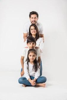 Heureuse famille indienne de 4 personnes isolées sur fond blanc. jeune couple avec enfants portant un haut blanc et un jean bleu. mise au point sélective