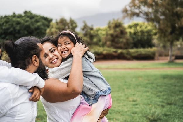 Heureuse famille indienne s'amusant en plein air au parc de la ville