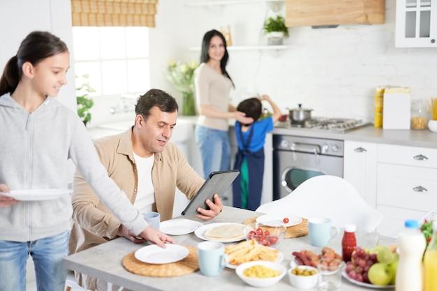 Heureuse famille latine en train de dîner à la maison. mari d'âge moyen utilisant une tablette, regardant les informations pendant que sa fille et sa femme servent la table, debout dans la cuisine