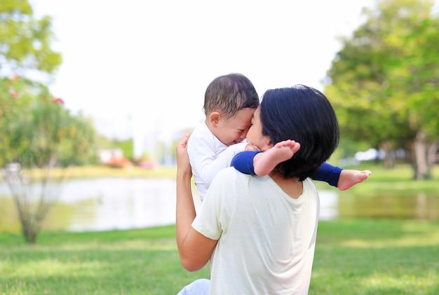 Heureuse famille maman asiatique et son fils jouant dans le jardin de la nature