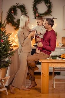 Heureuse famille maman papa fils se prépare pour la nouvelle année à la maison dans la cuisine.