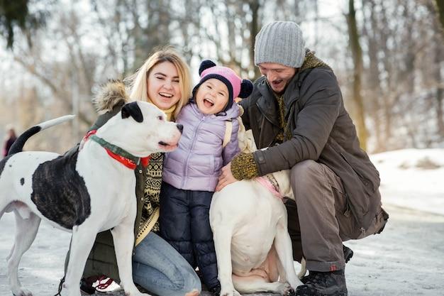 Heureuse famille de maman, papa et petite fille pose avec des bouledogues américains dans le parc