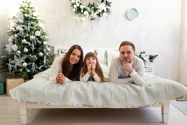 Heureuse famille mère père et enfants le matin de noël au lit