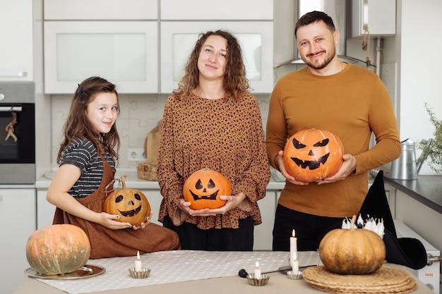 Heureuse famille mère père et fille célébration d'halloween à la maison