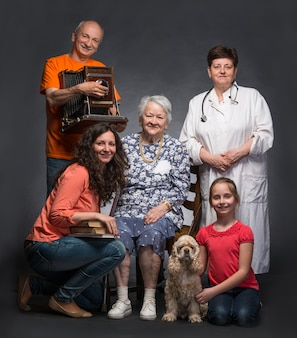 Heureuse famille multi-génération et chien de compagnie posant en studio sur un mur gris