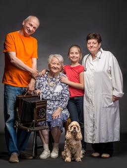 Heureuse famille multi-génération sur un mur gris