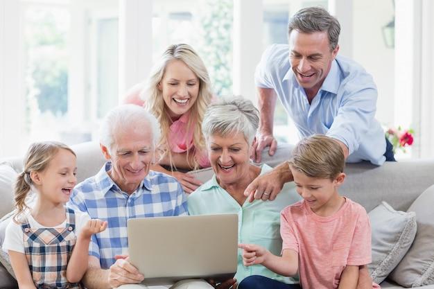 Heureuse famille multi-génération utilisant un ordinateur portable dans le salon