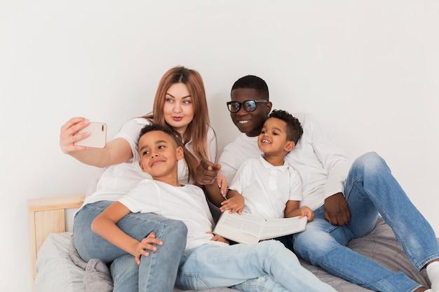 Heureuse famille multiculturelle prenant un selfie