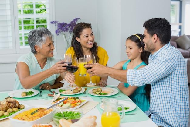 Heureuse famille de mutigénération griller un verre de vin rouge tout en prenant son repas