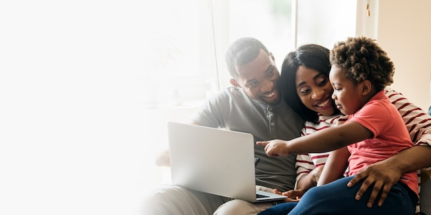 Heureuse famille noire et enfant en bas âge pointant sur un espace de conception d'écran d'ordinateur portable