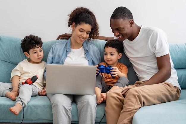 Heureuse famille noire regardant quelque chose sur un ordinateur portable et riant