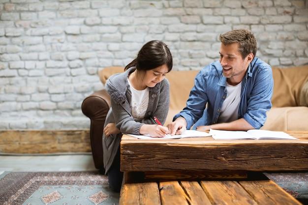Heureuse famille père et fille à faire leurs devoirs à la maison