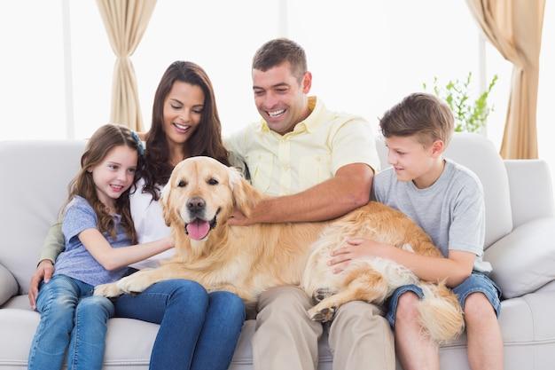 Heureuse famille de quatre caressant golden retriever dans le salon