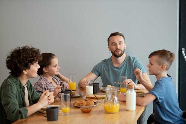 Heureuse famille de quatre personnes appréciant le petit-déjeuner à table servie dans la cuisine tout en regardant le petit garçon et en écoutant ses idées pour le week-end