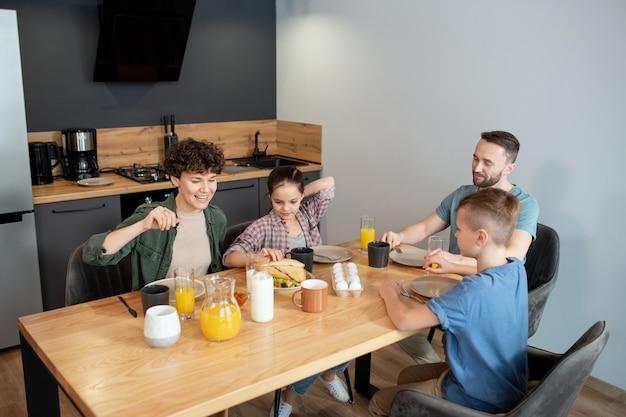 Heureuse famille de quatre personnes assises près d'une table en bois servie dans la cuisine et prendre le petit-déjeuner pendant qu'une fille prend un sandwich fait maison