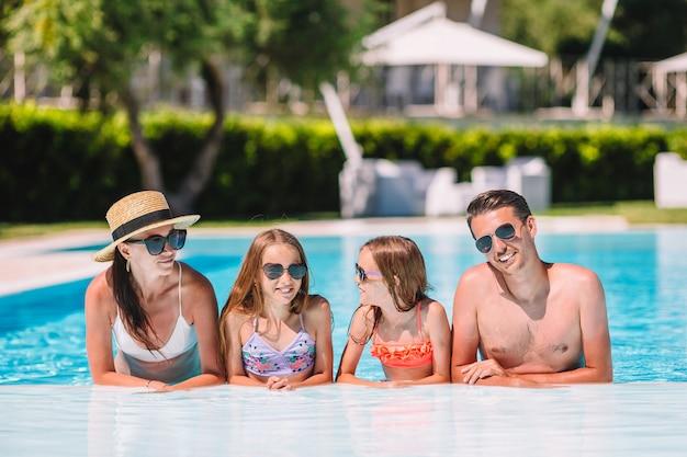 Heureuse famille de quatre personnes dans une piscine extérieure