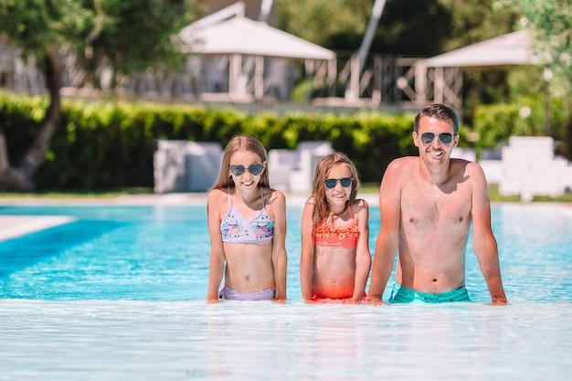 Heureuse famille de quatre personnes dans la piscine en plein air