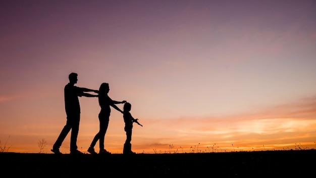Heureuse famille de quatre personnes, mère, père et fille dans le pré.