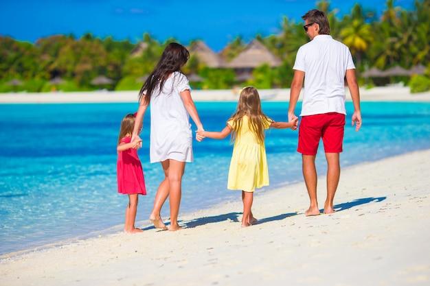 Heureuse famille de quatre personnes sur la plage blanche