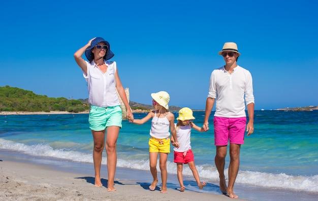 Heureuse famille de quatre personnes en vacances à la plage