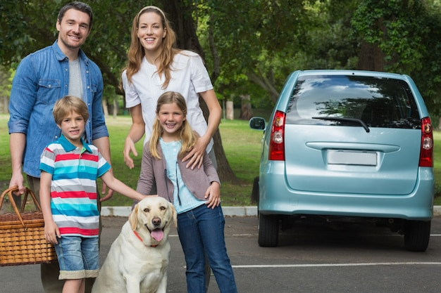 Heureuse famille de quatre personnes avec voiture en pique-nique