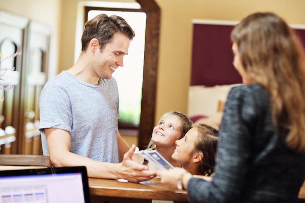 Heureuse famille s'enregistrant à l'hôtel à la réception