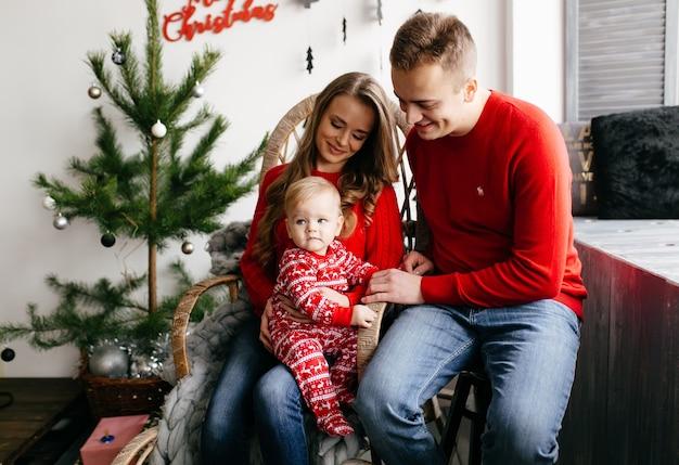 Heureuse famille souriante au studio sur fond de l'arbre de noël avec cadeau