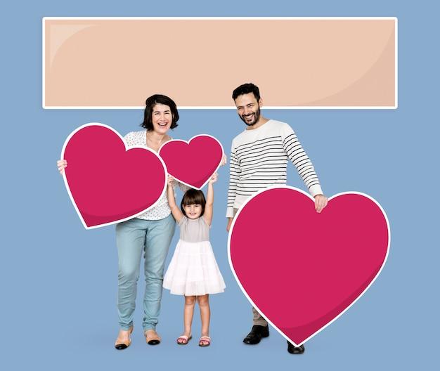 Heureuse famille tenant des icônes de coeur